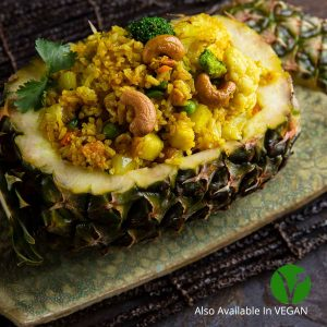 Pineapple fried rice with mixed vegetables, eggs, raisins & cashew nuts served in a pineapple shell